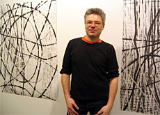 Oliver Krähenbühl with some of his charcoal drawings (swissinfo)